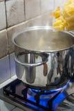 ρίξτε τα ζυμαρικά στο δοχείο του νερού στην πυρκαγιά σομπών στοκ εικόνα με δικαίωμα ελεύθερης χρήσης