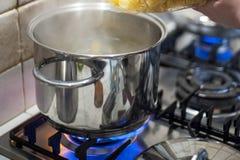 Ρίξτε τα ζυμαρικά στο δοχείο του νερού στην πυρκαγιά σομπών στοκ φωτογραφία με δικαίωμα ελεύθερης χρήσης