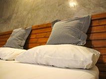 Ρίξτε τα μαξιλάρια και το μαξιλάρι στο άσπρο κρεβάτι στοκ φωτογραφία