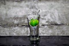 Ρίξτε τον ασβέστη σε ένα ποτήρι του νερού στοκ φωτογραφία