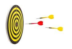Ρίχνοντας τα κόκκινα βέλη και τα κίτρινα βέλη πηγαίνουν στο bullseye dartboard, β Στοκ εικόνες με δικαίωμα ελεύθερης χρήσης