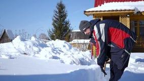 Ρίψη του χιονιού σε έναν σωρό Το άτομο με ένα φτυάρι σε δικοί του παραδίδει το μέτωπο του σπιτιού του ρίχνοντας το χιόνι σε έναν  απόθεμα βίντεο