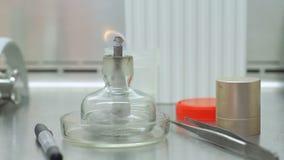 Ραβδί κεριών με την πυρκαγιά στον εργαστηριακό πίνακα Φλόγα πυρκαγιάς στην κούπα εργαστηρίων απόθεμα βίντεο