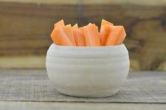 Ραβδί περικοπών του καρότου στο κύπελλο στο ξύλινο υπόβαθρο Στοκ Εικόνες