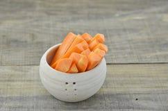 Ραβδί περικοπών του καρότου στο κύπελλο στο ξύλινο υπόβαθρο Στοκ φωτογραφία με δικαίωμα ελεύθερης χρήσης
