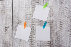 Ραβδί τριών σαφών εγγράφων στον ξύλινο πίνακα Άφθονος των κενών φύλλων που συνδέονται με την κατασκευασμένη σανίδα ξυλείας Δημιου στοκ εικόνα