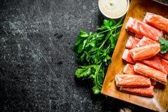 Ραβδιά καβουριών σε ένα ξύλινο πιάτο με τα πράσινα και τη σάλτσα στοκ φωτογραφίες με δικαίωμα ελεύθερης χρήσης