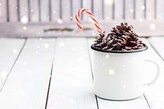 Ραβδιά καλάμων καραμελών Χριστουγέννων στο άσπρο φλυτζάνι κασσίτερου με τους κώνους έλατου Χρωματισμένη φως φωτογραφία Διάστημα γ στοκ φωτογραφίες με δικαίωμα ελεύθερης χρήσης
