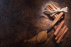 Ραβδιά κανέλας και σκόνη στο κουτάλι σε έναν παλαιό πίνακα χαλκού Στοκ Φωτογραφία
