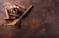 Ραβδιά κανέλας και σκόνη στο κουτάλι σε έναν παλαιό πίνακα χαλκού Στοκ εικόνες με δικαίωμα ελεύθερης χρήσης