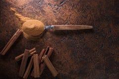 Ραβδιά κανέλας και σκόνη στο κουτάλι σε έναν παλαιό πίνακα χαλκού Στοκ Φωτογραφίες