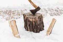 Ραβδιά τσεκουριών έξω στο κολόβωμα στο κλίμα του άσπρου χιονιού Στοκ εικόνες με δικαίωμα ελεύθερης χρήσης