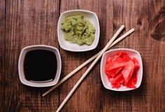Ραβδιά, Wasabi, σάλτσα σόγιας και παστωμένη πιπερόριζα για τα σούσια στο καφετί ξύλινο επιτραπέζιο υπόβαθρο Τοπ όψη Στοκ Εικόνα