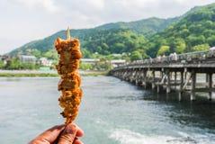 Ραβδί κοτόπουλου λαβής χεριών με τη γέφυρα togetsu-Kyo στο backgroun Στοκ Φωτογραφία