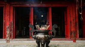 Ραβδιά θυμιάματος που καίνε στο γιγαντιαίο δοχείο μπροστά από το βουδιστικό ναό απόθεμα βίντεο