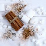 Ραβδιά κανέλας, snowflakes και marshmallows στο άσπρο υπόβαθρο Στοκ Εικόνες