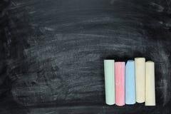 Ραβδιά της χρωματισμένης κιμωλίας σε έναν πίνακα κιμωλίας Στοκ Φωτογραφίες