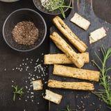 Ραβδιά ψωμιού από τη ζύμη ριπών με τους σπόρους λιναριού, τους σπόρους σουσαμιού, το άλας θάλασσας και το δεντρολίβανο σε ένα σκο Στοκ φωτογραφίες με δικαίωμα ελεύθερης χρήσης