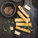 Ραβδιά ψωμιού από τη ζύμη ριπών με τους σπόρους λιναριού, τους σπόρους σουσαμιού, το άλας θάλασσας και το δεντρολίβανο σε ένα σκο Στοκ Εικόνες