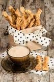 Ραβδιά ψωμιού τυριών σκόρδου και φλυτζάνι του μαύρου τσαγιού με το γάλα Στοκ Εικόνες