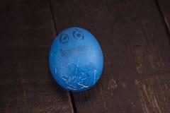 Ραγισμένα ζωηρόχρωμα αστεία αυγά Πάσχας σε έναν ξύλινο πίνακα Στοκ Εικόνα