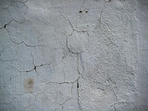 Ραγισμένος άσπρος χρωματισμένος τοίχος που εκτίθεται στην υπαίθρια σύσταση μορφών Στοκ Φωτογραφία