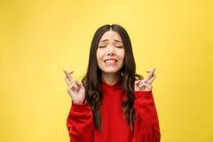 Ραδιουργημένη γυναίκα στην επίκληση με τα διασχισμένα δάχτυλα και το κοίταγμα μακριά πέρα από το κίτρινο υπόβαθρο στοκ φωτογραφίες με δικαίωμα ελεύθερης χρήσης
