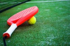 Ρακέτα αντισφαίρισης κουπιών, σφαίρα και καθαρός στη χλόη Στοκ Εικόνες