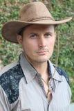 Ραπτικές κάουμποϋ Πορτρέτο του νεαρού άνδρα που φορά το καπέλο κάουμποϋ στεμένος στο φυσικό πράσινο κλίμα Στοκ Φωτογραφία