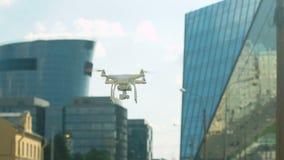 Ραδιο-ελεγχόμενος quadcopter αιωρείται πέρα από μια οδό στην πόλη απόθεμα βίντεο
