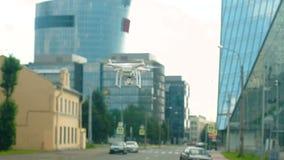Ραδιο-ελεγχόμενος quadcopter αιωρείται πέρα από μια οδό στην πόλη φιλμ μικρού μήκους