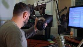 Ραδιο παρουσιαστής στο μικρόφωνο σε ένα ζωντανό στούντιο ραδιοφωνικής εκπομπής απόθεμα βίντεο
