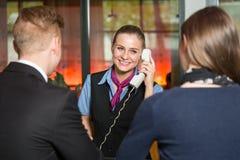 Ρεσεψιονίστ με τους τηλεφωνικούς βοηθώντας φιλοξενουμένους στο ξενοδοχείο Στοκ φωτογραφία με δικαίωμα ελεύθερης χρήσης