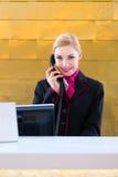 Ρεσεψιονίστ ξενοδοχείων με το τηλέφωνο στο μπροστινό γραφείο Στοκ Εικόνες