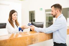 Ρεσεψιονίστ που παίρνει την πληρωμή με την πιστωτική κάρτα Στοκ φωτογραφία με δικαίωμα ελεύθερης χρήσης