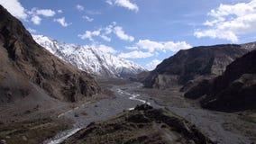 Ρεύμα βουνών στο κατώτατο σημείο του φαραγγιού στα βουνά Καύκασου, μπλε ουρανός, σταυρός στην άκρη του λόφου Άνοιξη, ηλιόλουστο w απόθεμα βίντεο