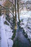 Ρεύμα που περιβάλλεται τα δέντρα και τους δρόμους που καλύπτονται από στο χιόνι κατά τη διάρκεια της θύελλας Emma Στοκ φωτογραφία με δικαίωμα ελεύθερης χρήσης