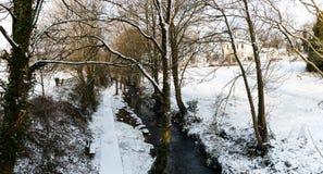 Ρεύμα που περιβάλλεται τα δέντρα και τους δρόμους που καλύπτονται από στο χιόνι κατά τη διάρκεια της θύελλας Emma Στοκ Εικόνες