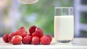 Ρεύμα του γάλακτος που χύνεται στο υαλουργικό υγιές θερινό πρόγευμα με τις οργανικές φράουλες φιλμ μικρού μήκους