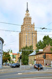 ΡΗΓΑ/ΛΕΤΟΝΙΑ - 27 Ιουλίου 2013: Οδός στην πόλη της Ρήγας με το ψηλό κτίριο της λετονικής ακαδημίας των επιστημών στο υπόβαθρο στοκ εικόνα
