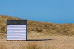 Ριγωτή καλύβα παραλιών στην αμμώδη παραλία Απομονωμένες διακοπές παραλιών Στοκ Εικόνες