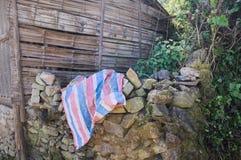 Ριγωτό ρόδινο, μπλε και άσπρο ύφασμα στις πέτρες σε μια αγροτική θέση Στοκ φωτογραφία με δικαίωμα ελεύθερης χρήσης