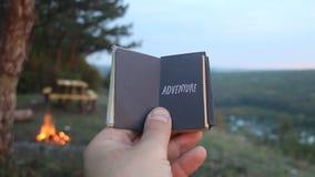 ριψοκινδυνεμμένο Βιβλίο με την επιγραφή και το δασικό βουνό Ταξίδι ή διακινούμενη ιδέα απόθεμα βίντεο