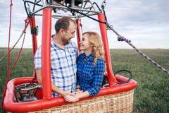 ριψοκινδυνεμμένο Όμορφο ρομαντικό ζεύγος που αγκαλιάζει στο μπαλόνι ζεστού αέρα bascket στοκ εικόνες