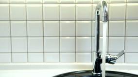Ροές καθαρού νερού από τη βρύση μετάλλων στο λουτρό στο διαμέρισμα φιλμ μικρού μήκους