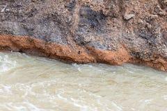 Ροές νερού στο αμμοχάλικο, βράχοι, κάτω από το δρόμο Στοκ φωτογραφία με δικαίωμα ελεύθερης χρήσης
