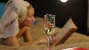 Ροές σαμπάνιας κινηματογραφήσεων σε πρώτο πλάνο σε ένα γυαλί Η όμορφη στήριξη νέων κοριτσιών άνετα σε ένα κρεβάτι και διαβάζει έν φιλμ μικρού μήκους