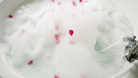 Ροές του νερού από τη βρύση σε ένα λουτρό με τον αφρό φιλμ μικρού μήκους