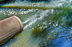 Ροές του νερού από το σωλήνα στον ποταμό Στοκ Εικόνες