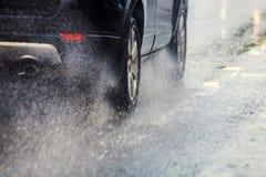 Ροή παφλασμών νερού βροχής από τις ρόδες του μαύρου αυτοκινήτου που κινούνται γρήγορα στην πόλη φωτός της ημέρας με την εκλεκτική στοκ εικόνα με δικαίωμα ελεύθερης χρήσης
